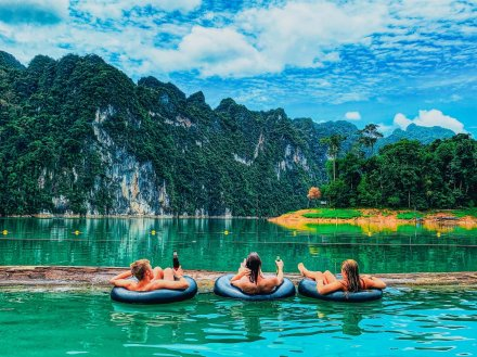 A trio admiring the view of Khao Sok national park in Thailand from doughnuts in the water