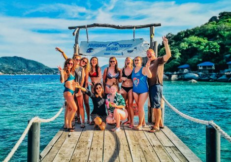 Group photo by crystal clear blue waters in Koh Tao