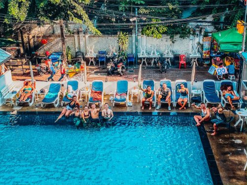 Groups enjoying a drink sat around a pool raising their arms to cheer with a busy market street in the background
