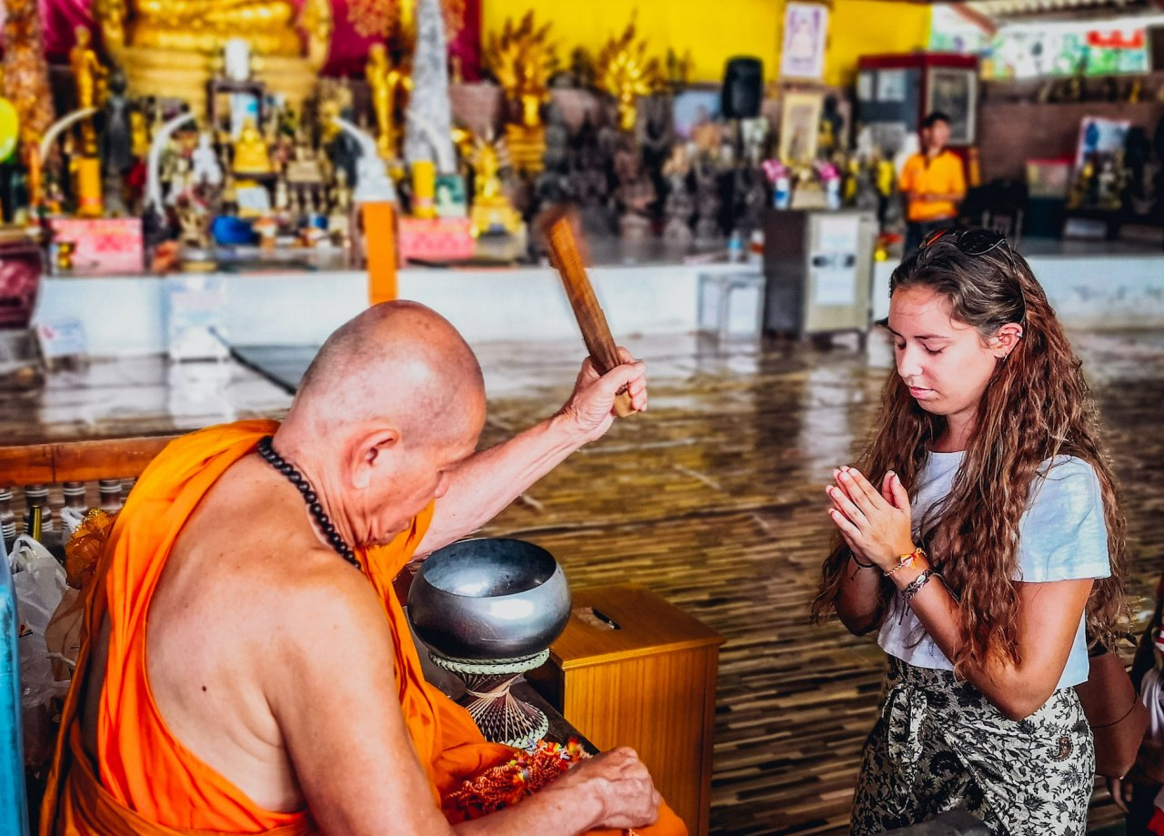 A girl being blessed by a monk in Phuket Thailand