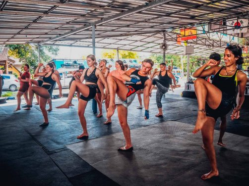 group learning how to do muay thai in Thailand with knee up to elbow