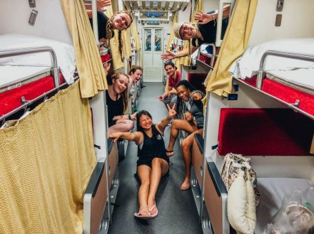 Group hanging out from bunk beds on an overnight train in Thailand with one girl sitting on the floor.