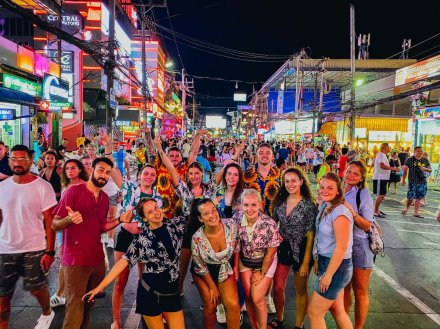 large group of friends on a night out in Phuket with lots of colours from shops and bars in the background