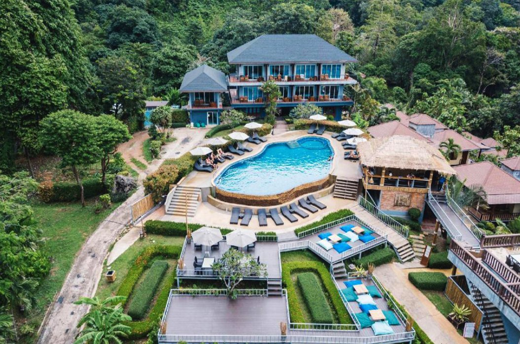 A drone shot of the hotel grounds in Railay beach, Krabi, Thailand showing the pool, sun loungers, bean bags and luscious surrounding greenery