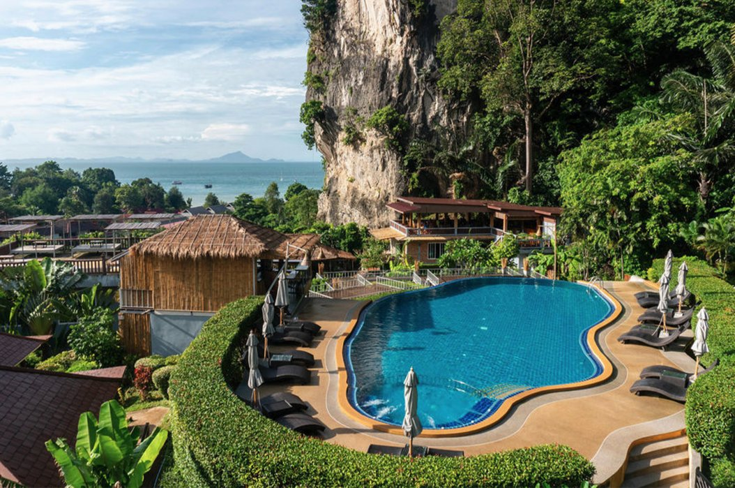 A photo of a hotel in Railay beach, Krabi, Thailand showing the blue pool, sun loungers and the surrounding lush greenery