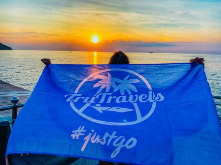 A girl holding a TruTravels flag by the beach with a stunning sunset in Thailand