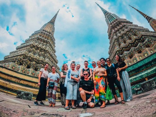 Group standing in between two temples in Bangkok with blue sky and clouds