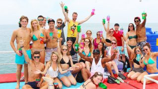 large group of people on a boat holing beers in the air in Thailand