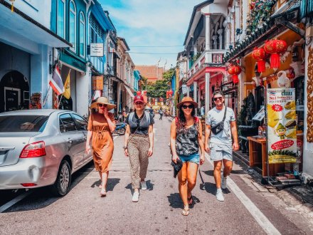A group of four walking through the streets of Phuket, Thailand