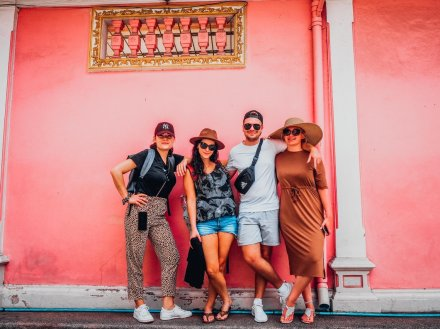 A group of four posing in front of a bright pink wall in Phuket, Thailand