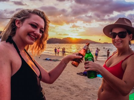 Two girls toasting their beers on the beach at sunset in Phuket, Thailand