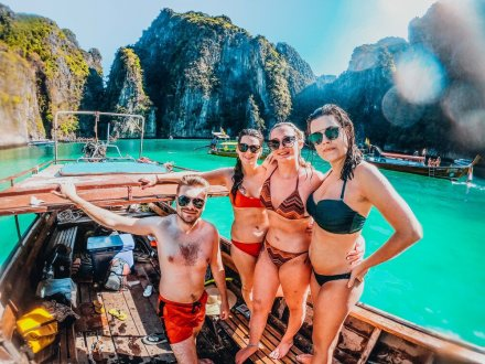 A group of four on a long tail boat in Koh Phi Phi, Thailand surrounded by lush greenery, cliffs and stunning turquoise water
