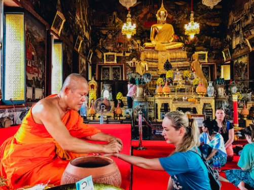A girl being blessed by a monk at the temples in Bangkok Thailand