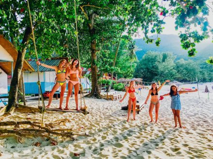 Five girls at bottle beach in Koh Phangan with two of them on the swing
