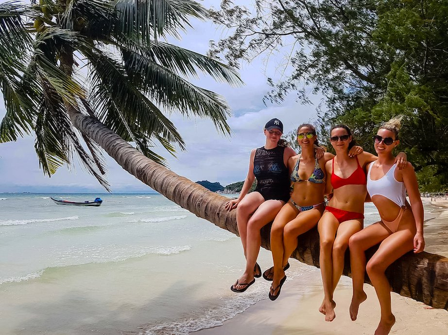 Girls sitting on palm tree on the beach, Thailand