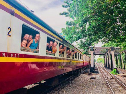 A group photo from the windows on the overnight train to Khao Sok National Park Thailand