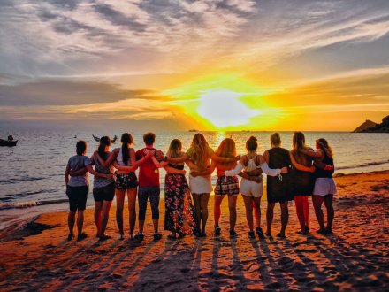 A group photo at sunset on the beach in Thailand