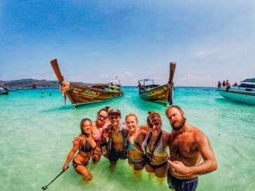 A group selfie in the crystal clear water by the long tail boats in West Thailand