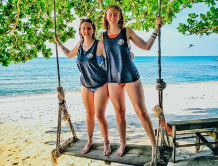 Two girls on a swing at the idyllic bottle beach Koh Phangan Thailand