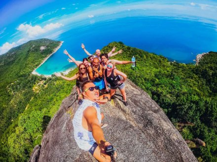 A group using a selfie stick at the top of the view point at bottle beach in Koh Phangan Thailand overlooking the lush greenery and blue sea