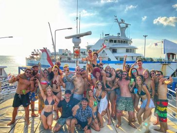 Big group of travellers having fun outside in front of a boat in Thailand